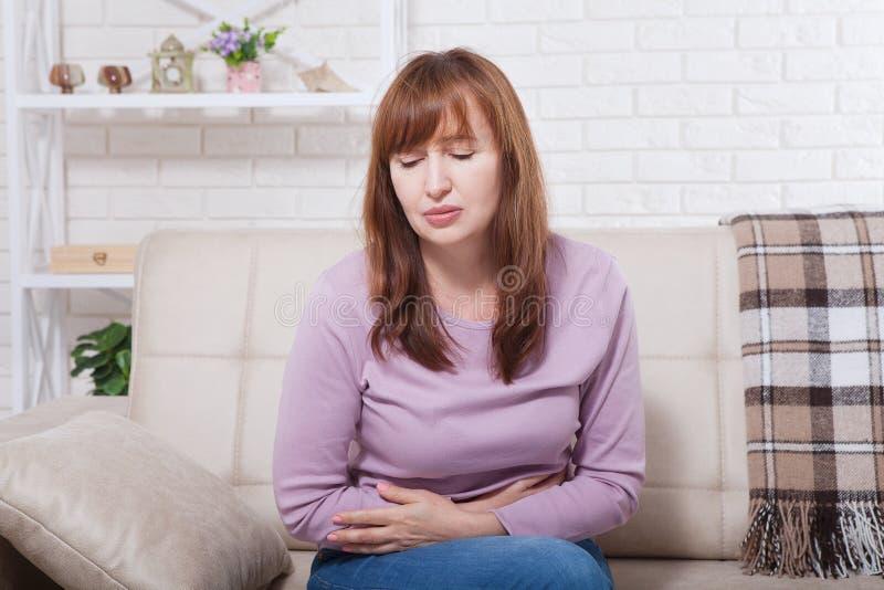 中年妇女有月经期间胃痛在家背景 复制空间并且嘲笑  更年期概念 免版税库存图片