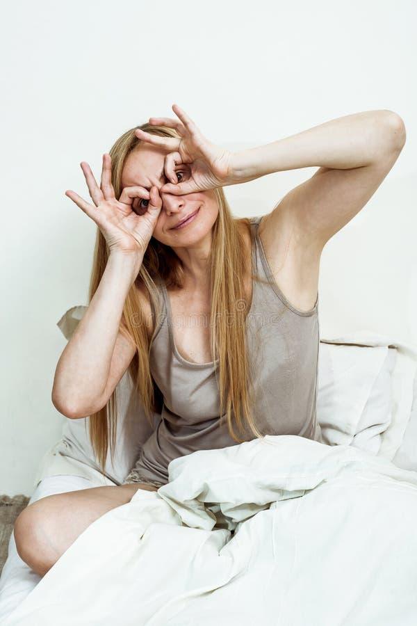 中年妇女真正画象床卧室白肤金发长头发五十正拷贝空间50一揽子枕头面孔 库存照片