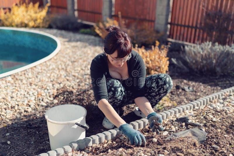 中年妇女花匠在春天庭院里 库存图片