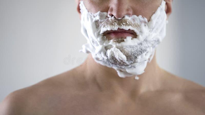 中年男性失望和恼怒由于新的刮的泡沫的质量 免版税库存照片
