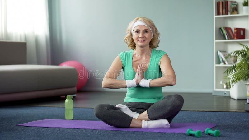 中年白肤金发的女性实践的莲花姿势在家,做瑜伽行使 免版税图库摄影
