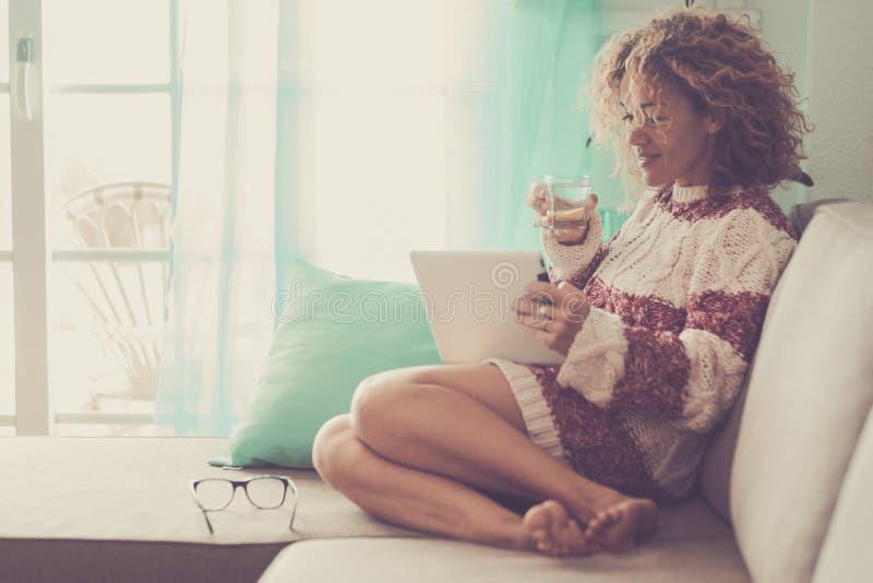 中年美丽的式样妇女在家坐读ebook的沙发在片剂和互联网有关 ?? 免版税库存照片