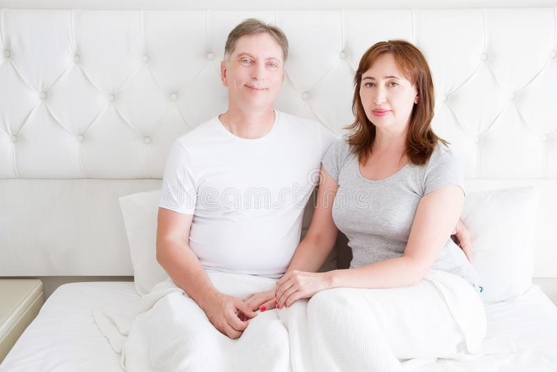 中年资深夫妇在床上 模板和空白的T恤杉 正面图 健康关系 复制空间 免版税库存照片