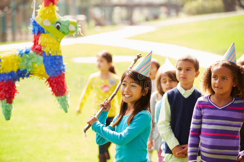 击中彩饰陶罐的孩子在生日聚会 免版税图库摄影