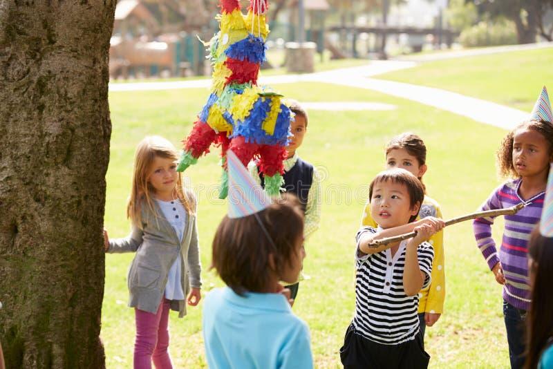 击中彩饰陶罐的孩子在生日聚会 库存照片
