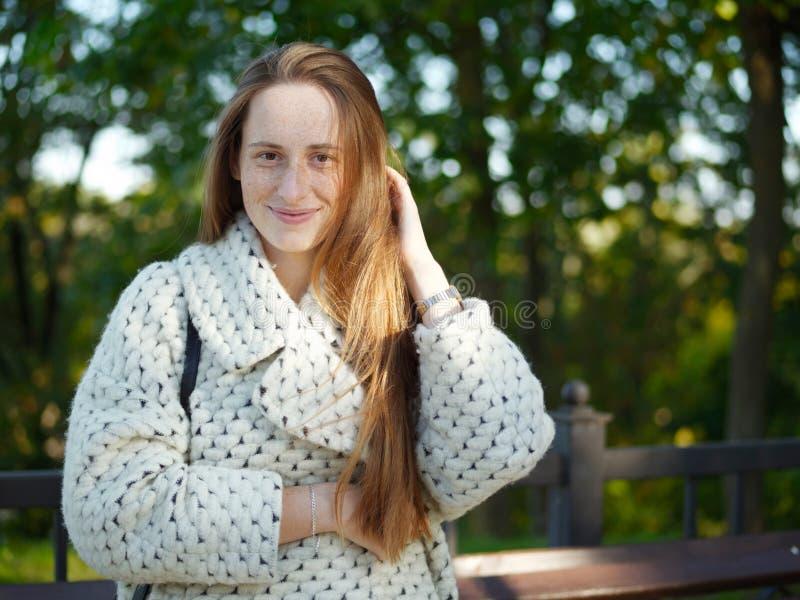 中景年轻时髦穿戴的严肃白种人妇女摆在室外在都市城市公园被弄脏的背景冷天 免版税图库摄影