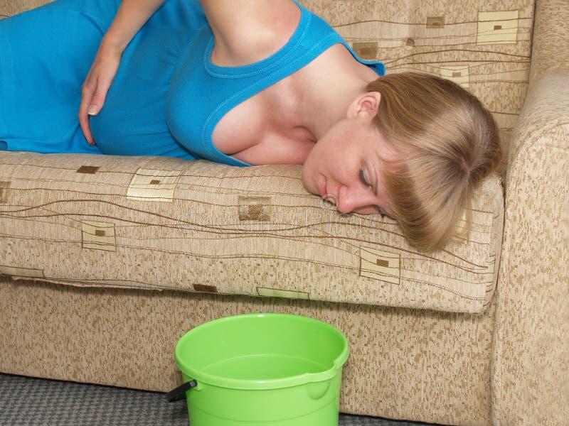 中毒的 孕妇在沙发说谎 免版税库存图片