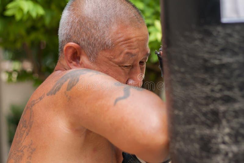 击中沙袋的泰国拳击手 库存照片