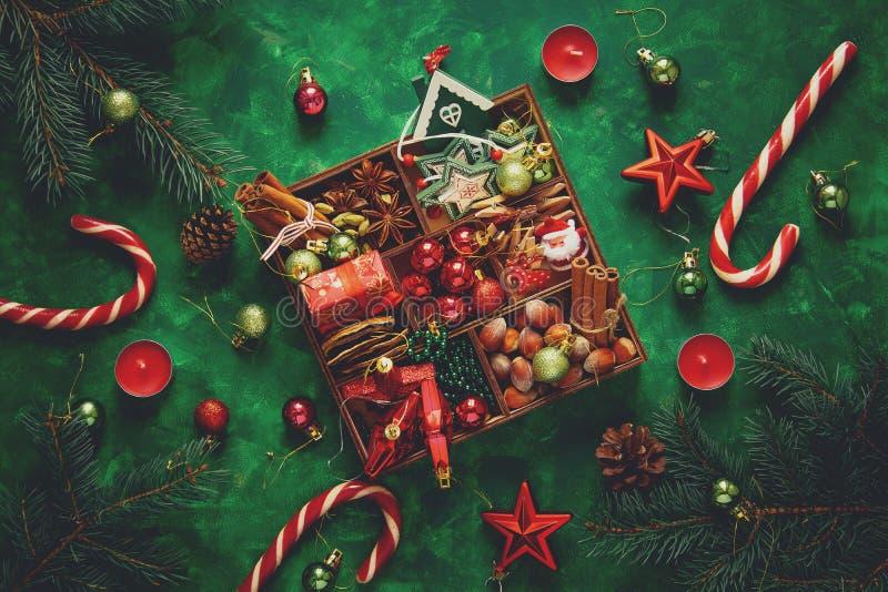 中看不中用的物品蓝色圣诞节构成玻璃 圣诞树和箱子用香料和玩具在绿色木背景 免版税库存照片