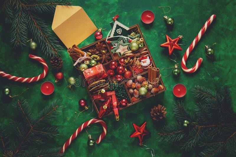 中看不中用的物品蓝色圣诞节构成玻璃 圣诞树和箱子用香料和玩具在绿色木背景 库存图片
