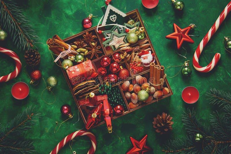中看不中用的物品蓝色圣诞节构成玻璃 圣诞树和箱子用香料和玩具在绿色木背景 库存照片