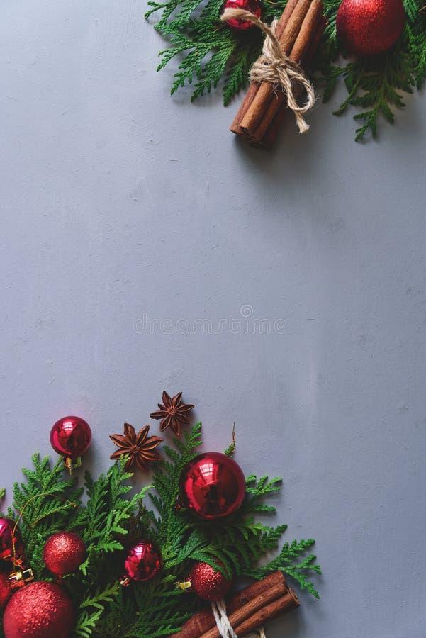 中看不中用的物品蓝色圣诞节构成玻璃 圣诞节杉树分支、球、肉桂条和茴香星在灰色木背景 平的位置 免版税图库摄影