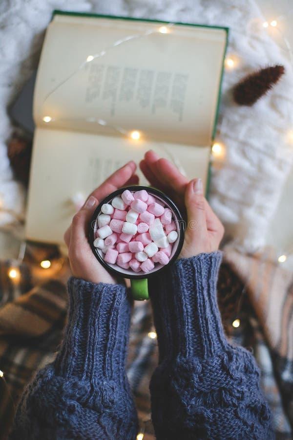 中看不中用的物品蓝色圣诞节构成玻璃 在拿着在书的毛线衣的女性手一个杯子 平的位置 免版税库存照片