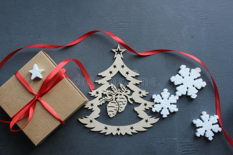 中看不中用的物品蓝色圣诞节构成玻璃 有红色缎丝带、树和雪花的礼物盒在黑背景 库存照片