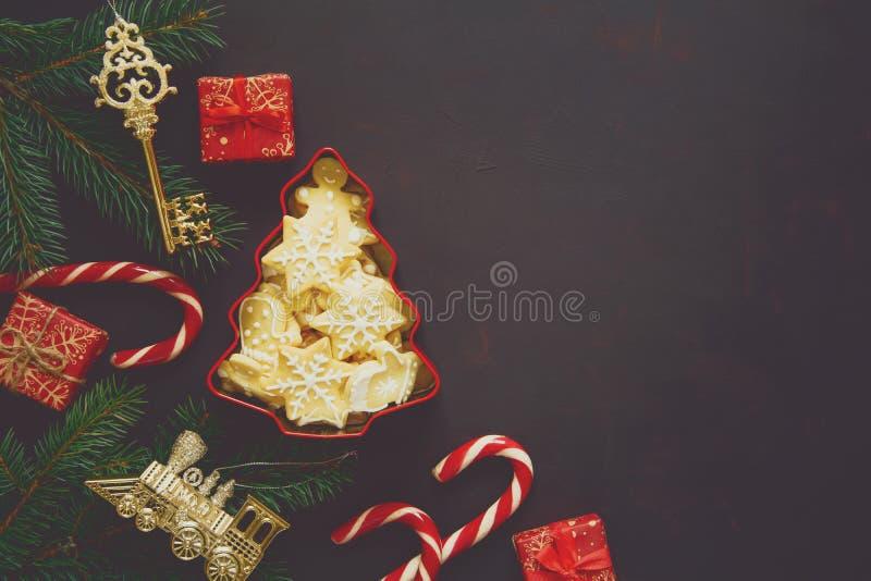 中看不中用的物品蓝色圣诞节构成玻璃 圣诞树、姜饼曲奇饼、礼物盒、甜藤茎和玩具在黑暗的木背景 图库摄影