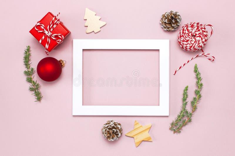 中看不中用的物品蓝色圣诞节构成玻璃 白色照片框架,冷杉分支,锥体,红色球,麻线,礼物,在桃红色背景舱内甲板的木玩具放置上面 免版税库存图片