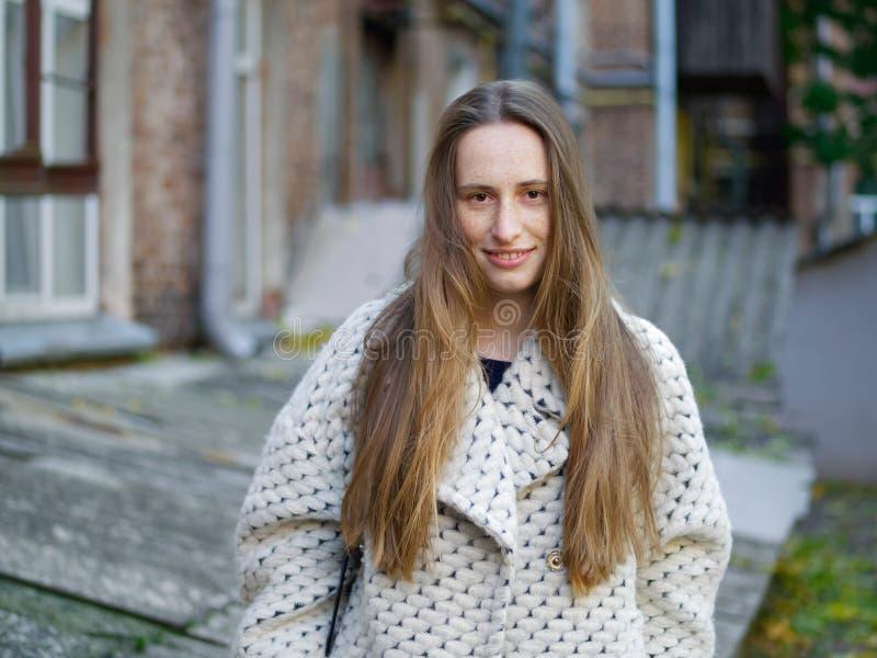 中等轻率冒险年轻时髦穿戴的严肃白种人妇女摆在室外在老城市围场背景冷天 库存图片