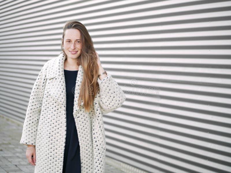 中等轻率冒险年轻时髦穿戴的严肃白种人妇女摆在室外在都市城市被弄脏的几何背景寒冷 免版税库存照片