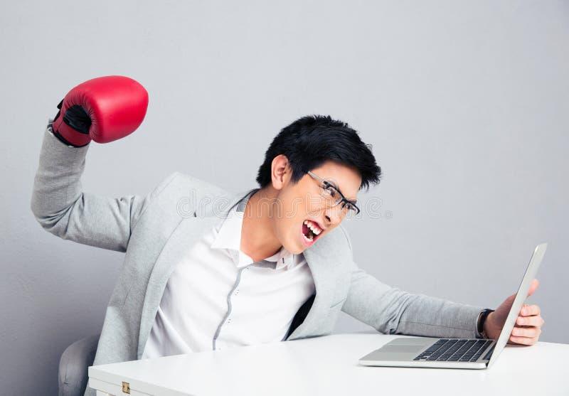 击中膝上型计算机的恼怒的商人读书 免版税库存照片
