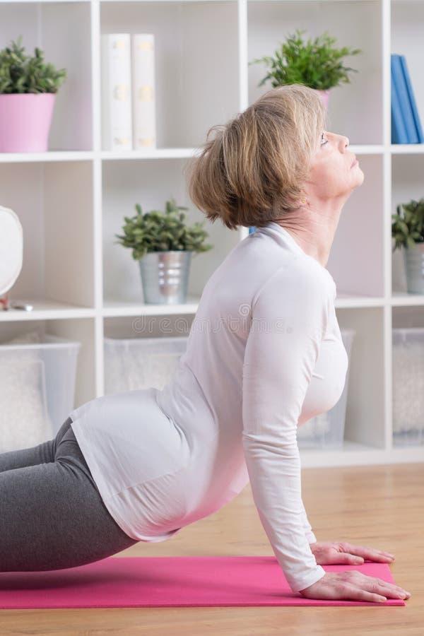 中部做瑜伽的年迈的妇女 免版税库存照片