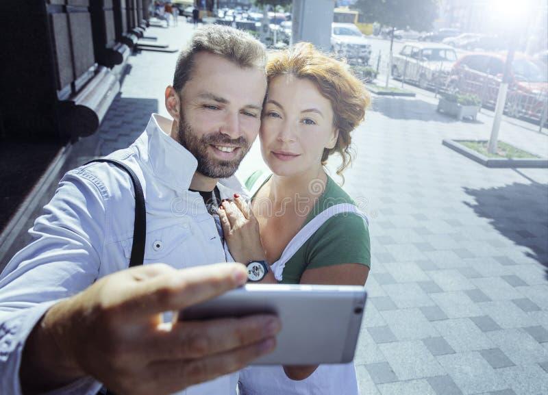 中部变老了做selfie在智能手机,天的夫妇,室外 免版税库存照片