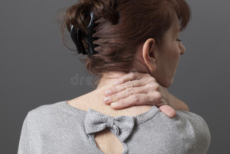中部变老了充满后面或脖子痛的夫人 免版税图库摄影