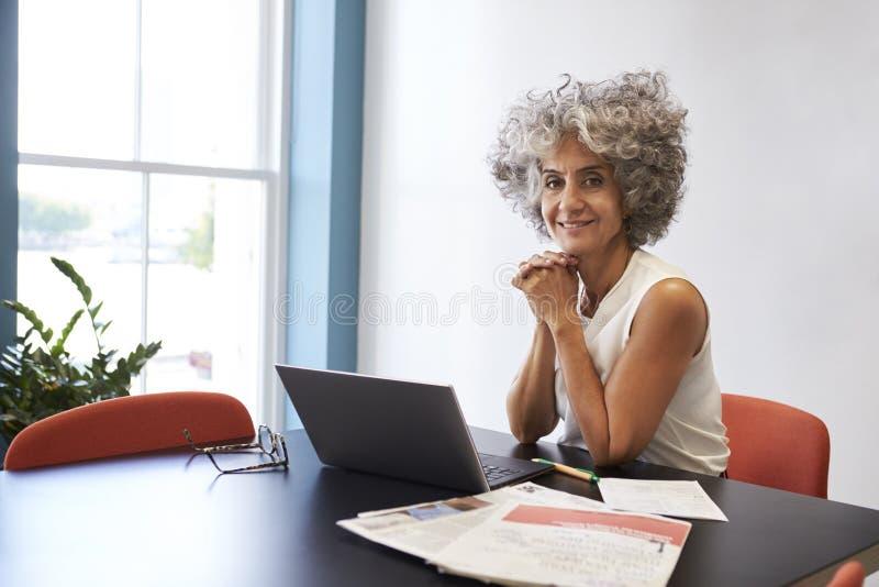 中部变老了工作在办公室的妇女微笑对照相机 图库摄影