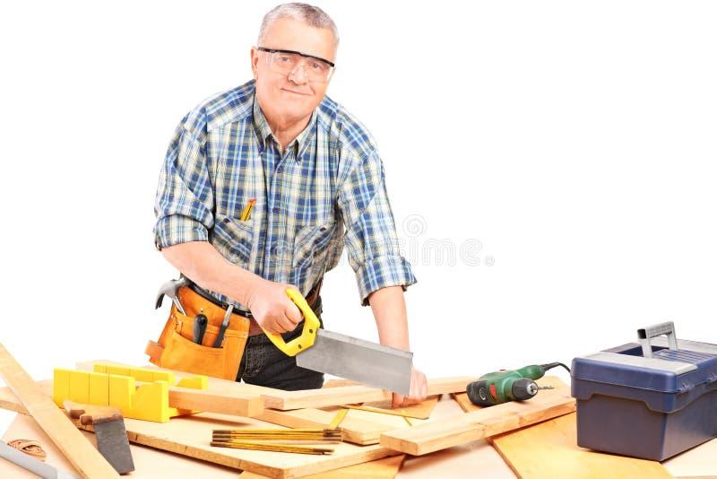 中部变老了工作在车间的男性木匠 免版税库存照片