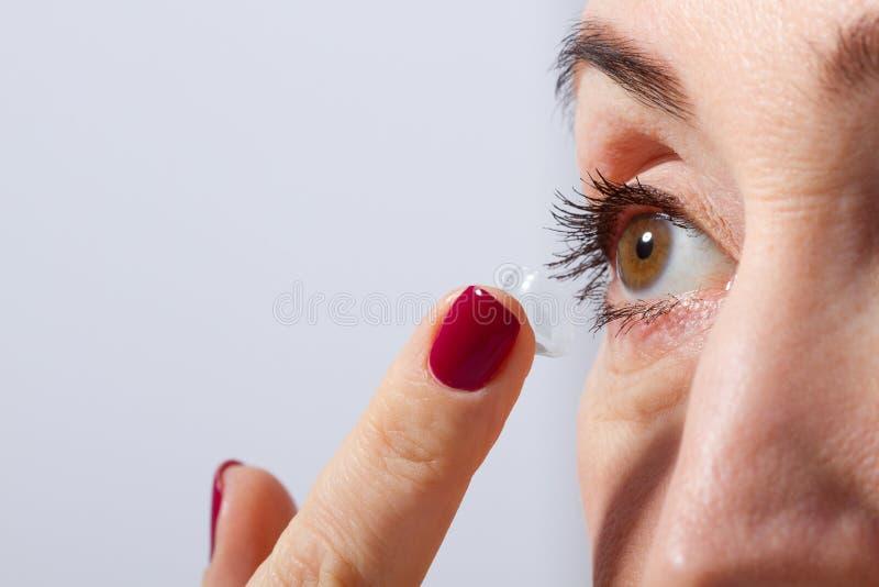 中部变老了应用或投入视觉的妇女隐形眼镜在她的棕色眼睛由手指 和被隔绝的关闭 选择聚焦a 图库摄影