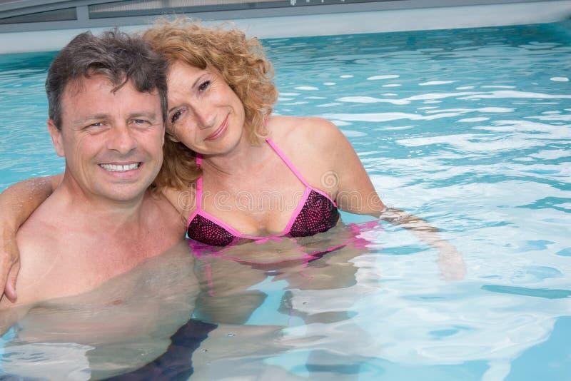中部变老了沐浴在游泳池的有吸引力的夫妇 免版税库存照片