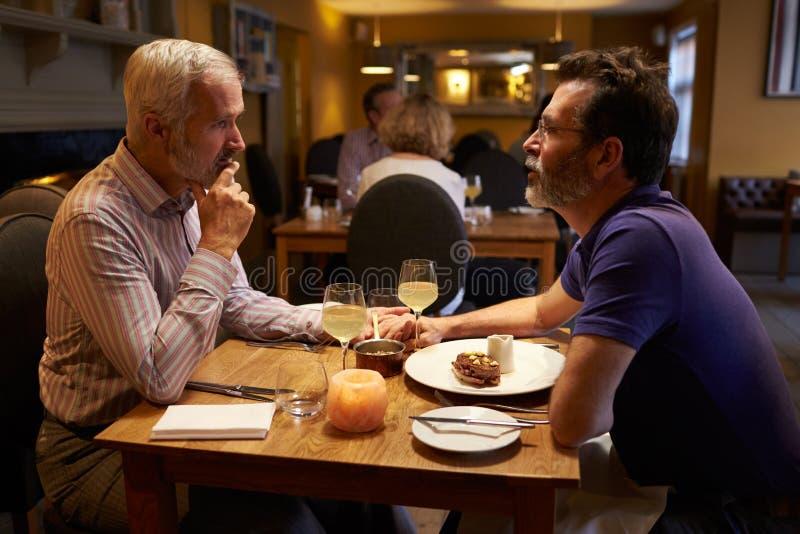 中部变老了男性夫妇有晚餐在餐馆 库存照片