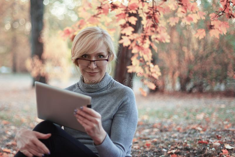 中部变老了白种人妇女在有片剂的金黄秋天公园单独坐,微笑 便衣,玻璃 珍贵的年龄概念 免版税库存图片