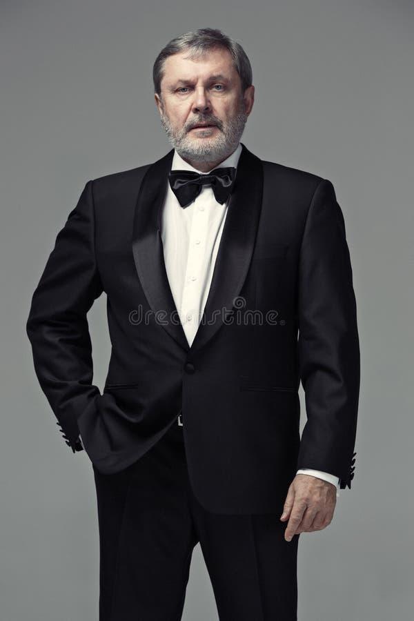 中部变老了穿着在灰色的男性成人衣服 免版税图库摄影