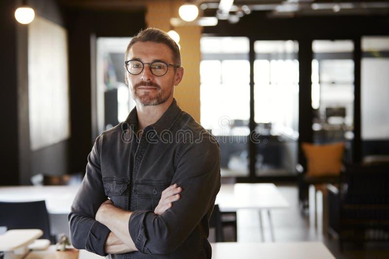 中部变老了站立在办公室的白色男性创造性的戴着眼镜查寻对照相机,腰部 免版税图库摄影