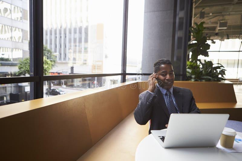 中部变老了黑商人使用电话在一个现代办公室 免版税库存照片