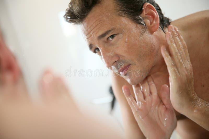 中部变老了洗他的面孔的镜子的人 库存图片