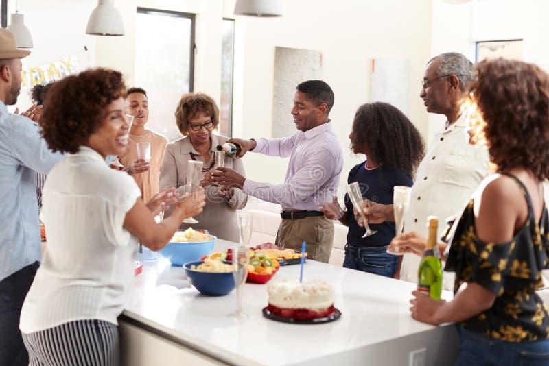中部变老非裔美国人的人倾吐的香槟在家庆祝与他的三一代家庭 免版税图库摄影