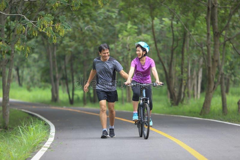 中部在公园变老了走与他们的自行车的夫妇 库存照片