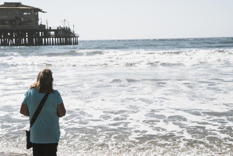 中部她的60s的年迈的资深妇女沿海岸线走在圣塔蒙尼卡加利福尼亚 免版税库存图片