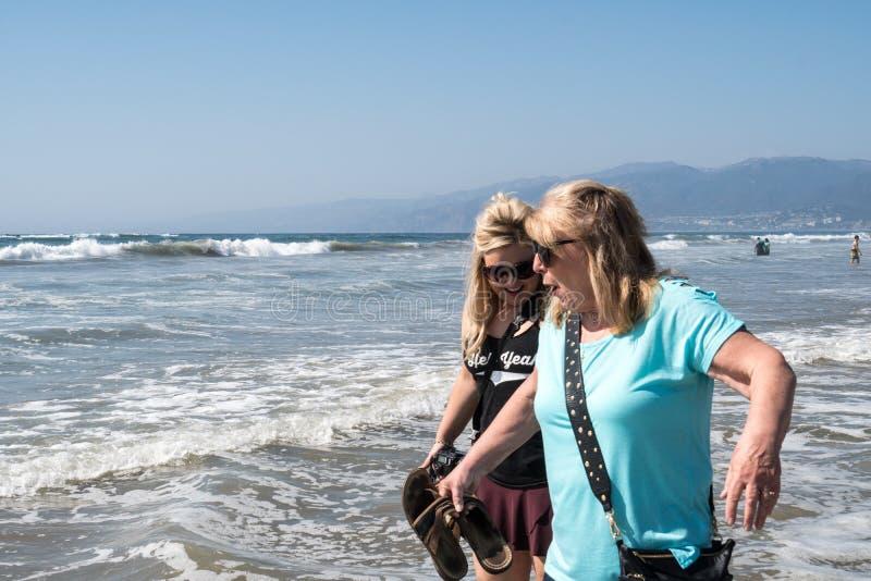 中部她的60s的年迈的资深妇女沿海岸线走在有她白肤金发的成人女儿的圣塔蒙尼卡加利福尼亚 免版税库存图片