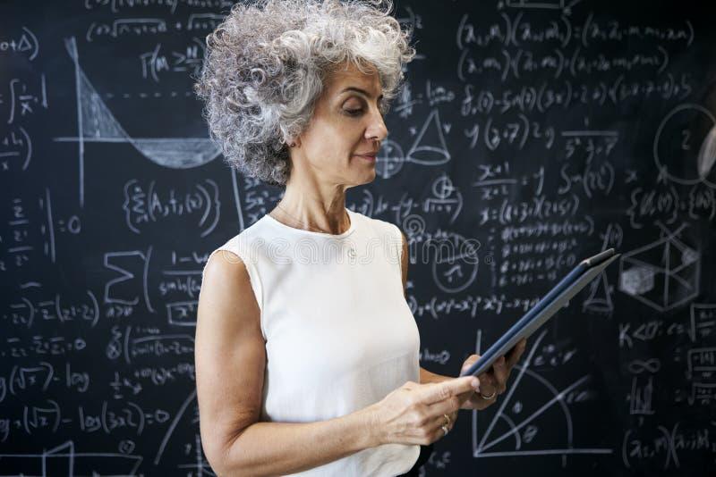 中部工作在黑板的年迈的学术妇女 免版税图库摄影