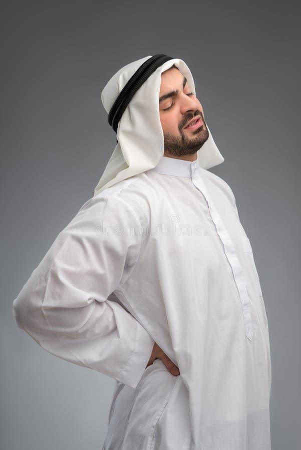 中部接触他酸疼的腰部的年迈的阿拉伯人 库存图片