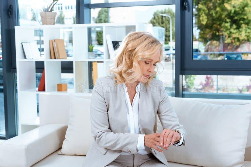 中部检查手表的年迈的女实业家 免版税库存图片