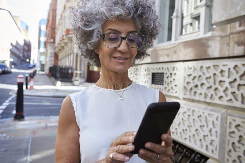 中部用完智能手机的年迈的妇女在城市街道,关闭 免版税库存图片