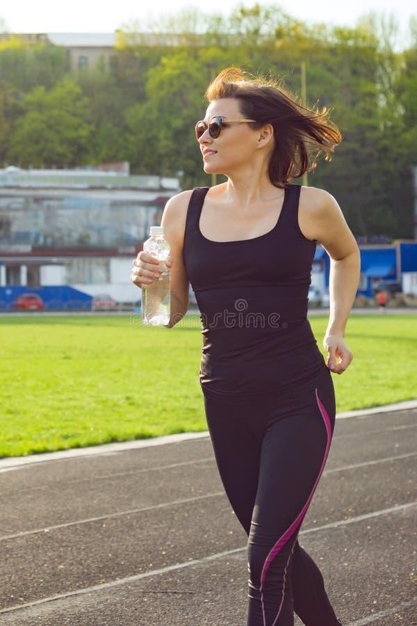 中部画象在体育场内变老了跑与瓶的妇女水在晚上 免版税图库摄影