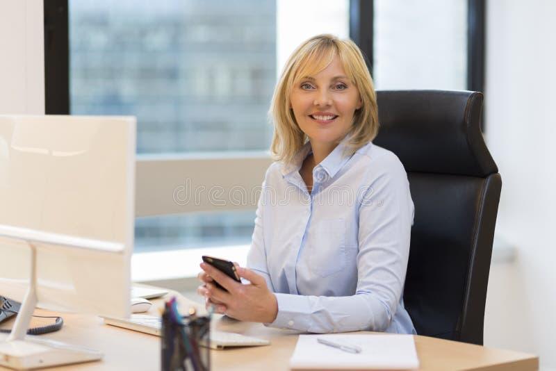 中部的画象变老了工作在办公室的女商人 库存照片