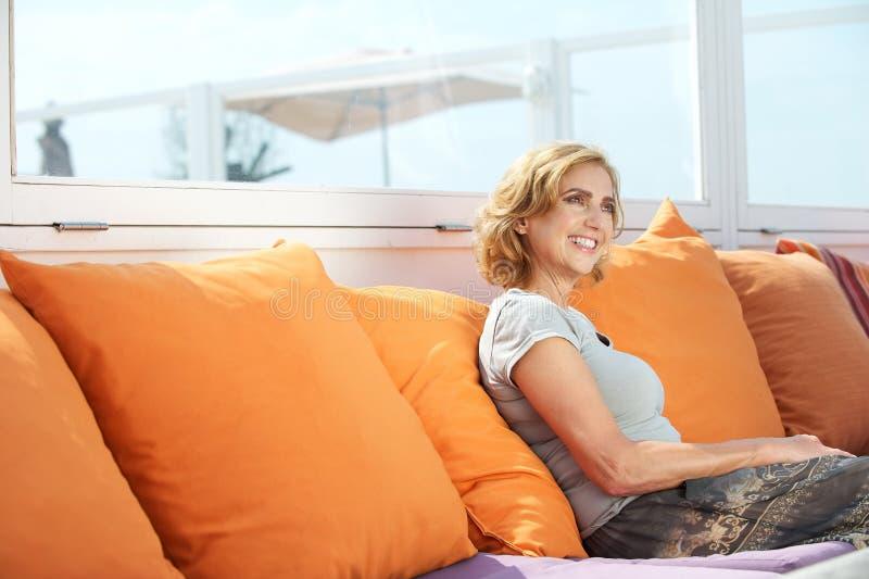 中部年迈的妇女坐沙发户外 免版税库存照片