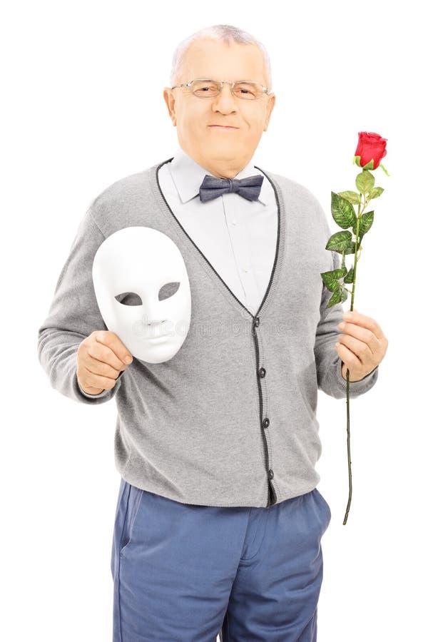 中部年迈的绅士藏品玫瑰色花和面具 图库摄影