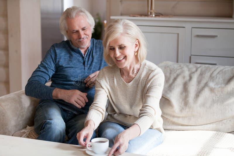 中间年迈的夫妇坐长沙发休息的饮用的茶 库存图片