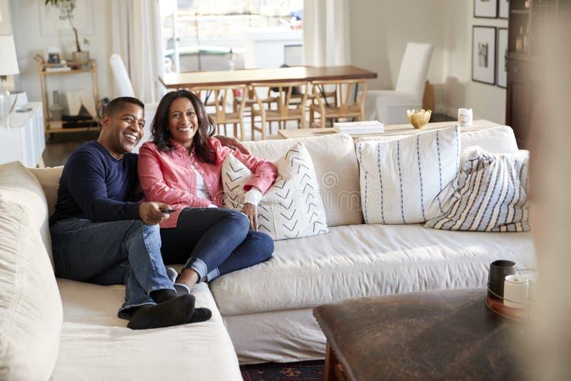 中间年迈的夫妇斜倚在他们的客厅看着电视的沙发的,选择聚焦 免版税库存图片